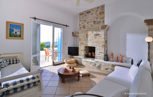 Griechenland - CYCLADES - MYKONOS - Lia - Villa Anastasia - Cozy living room with fireplace and access to terrace