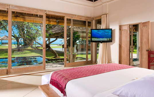 Asien - BALI - Legian - Villa Atas Ombak - Double bedroom with large windows offering views of the garden, pool and beach