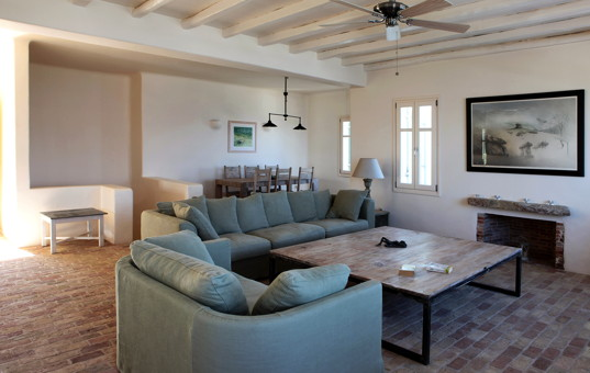 Griechenland - CYCLADES - ANTIPAROS - Soros - Soros Beach Villa 2 - Large living room with sofas surrounding the fireplace