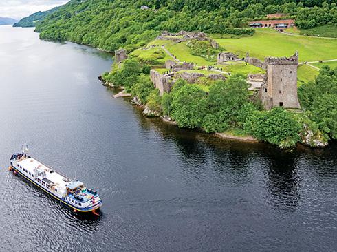 Hotel barging cruising past Urquhart castle Scotland